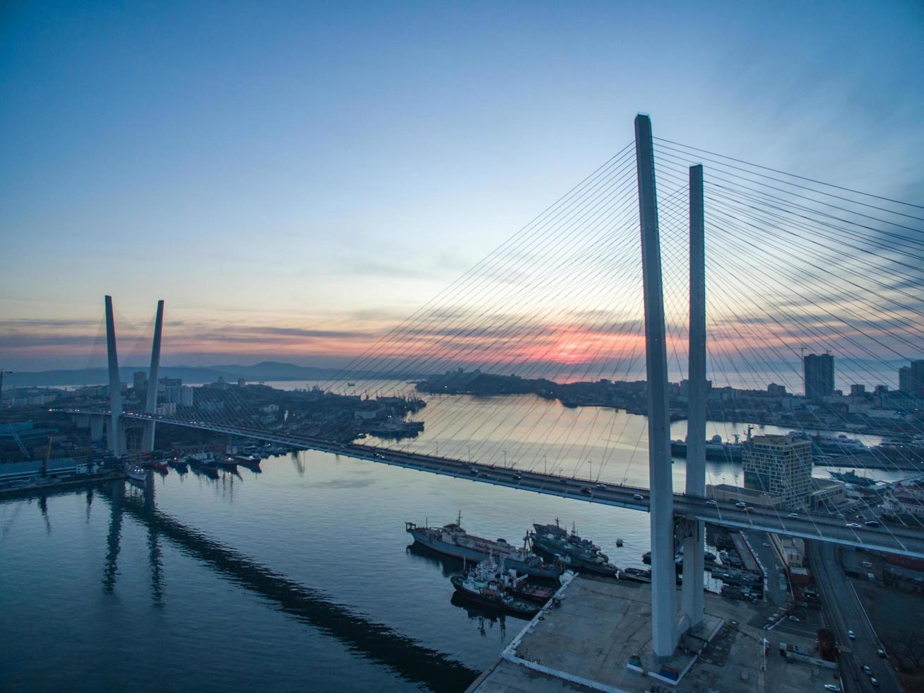 Zolotoy-Brücke und Wasser gegen bewölkten Sonnenunterganghimmel in Wladiwostok, Russland foto