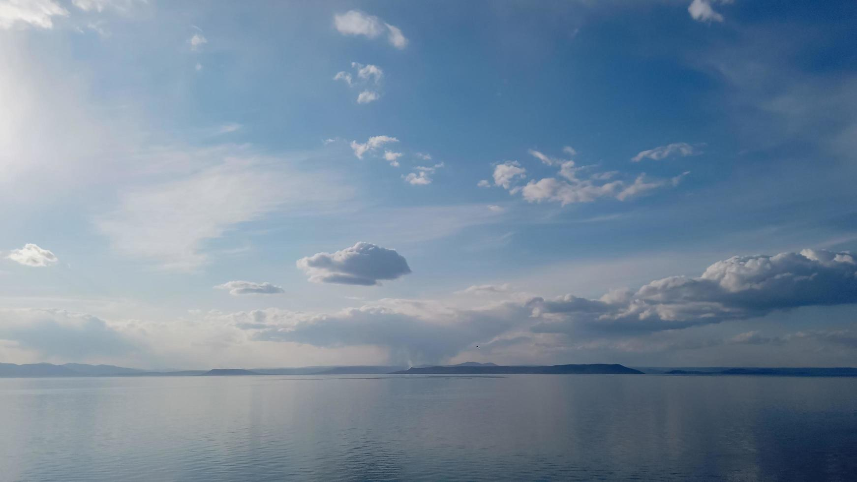 Seelandschaft des Gewässers mit bewölktem blauem Himmel foto