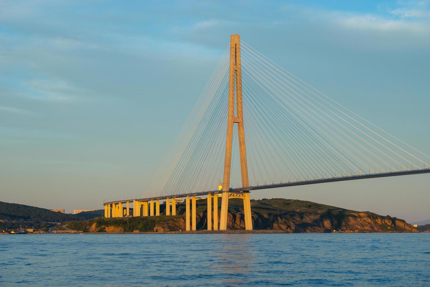 Seestück der goldenen Hornbucht und der Zolotoybrücke mit bewölktem blauem Himmel in Wladiwostok, Russland foto