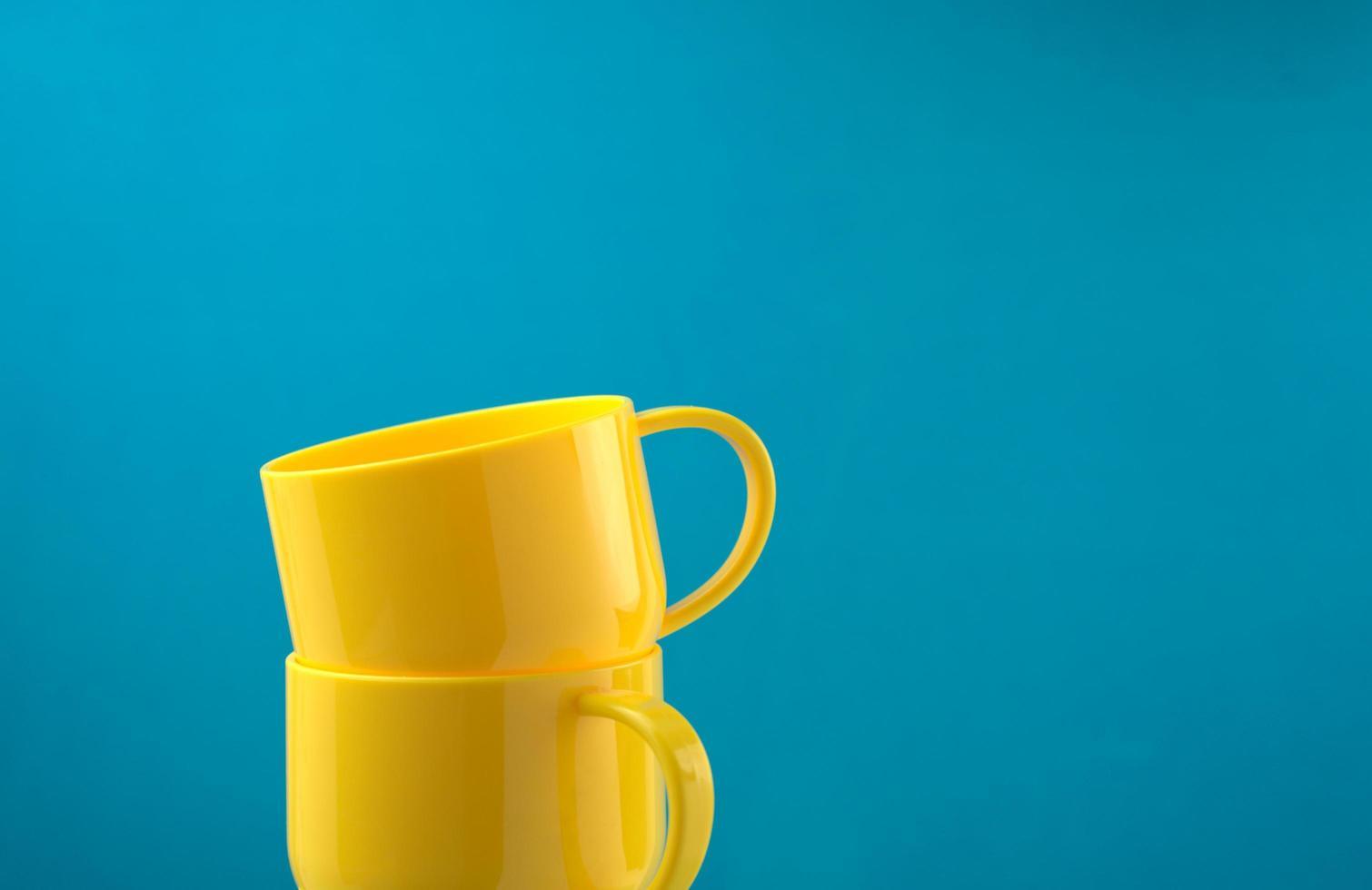 glänzende gelb gefärbte Tassen, die auf blauem Hintergrund stapeln foto