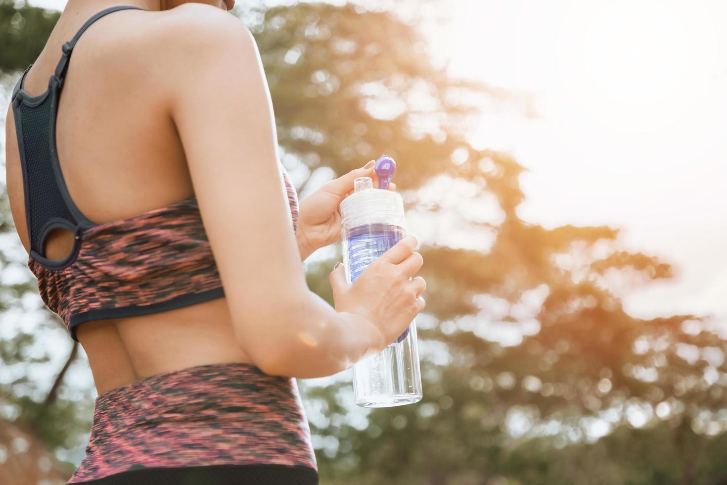ein weiblicher Läufer, der draußen steht und eine Wasserflasche hält, gesundes und Sportkonzept foto