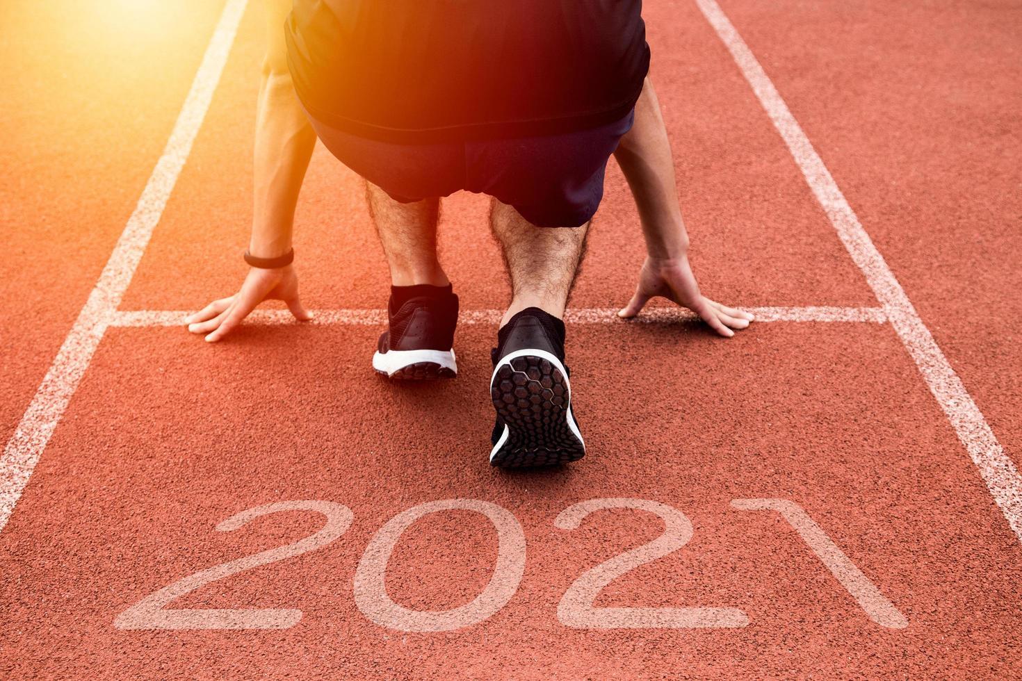 neues Jahr oder gerade Konzept beginnen. Nahaufnahme eines Athletenläufers, der zum Erfolg und zu neuen Errungenschaften auf dem Weg mit Inschrift 2021 läuft foto