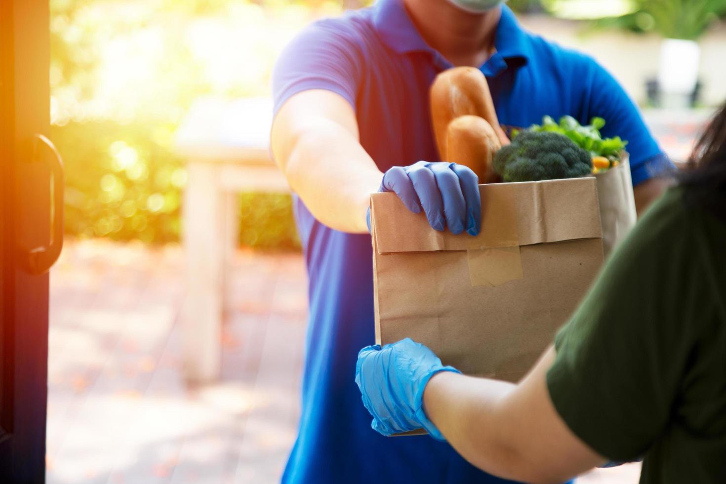 Foodservice-Anbieter mit Masken und Handschuhen. Zu Hause bleiben reduziert die Ausbreitung des Covid-19-Virus foto