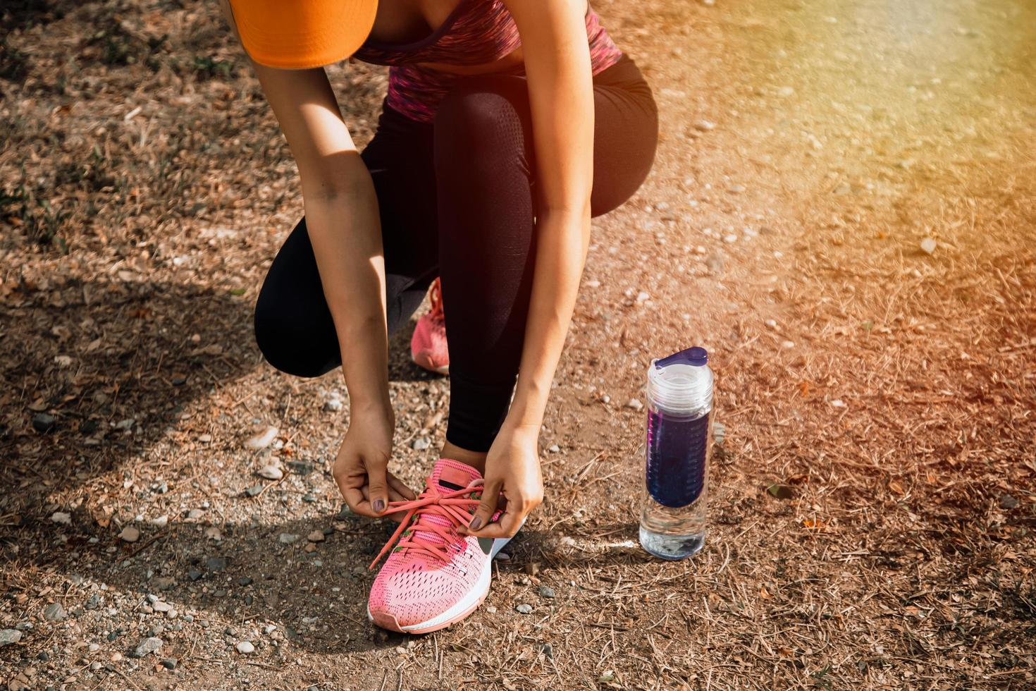 junge fitte Frau, die für Fitnesslauf im Park vorbereitet foto