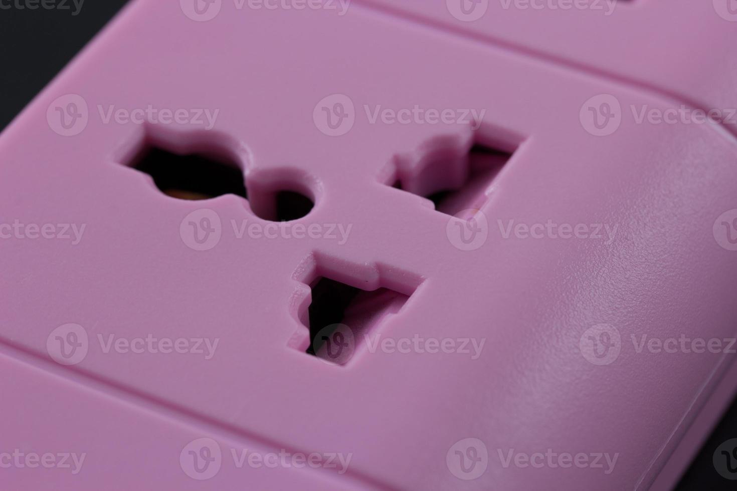 Nahaufnahmebild einer rosa Steckdose auf Schwarz isoliert foto