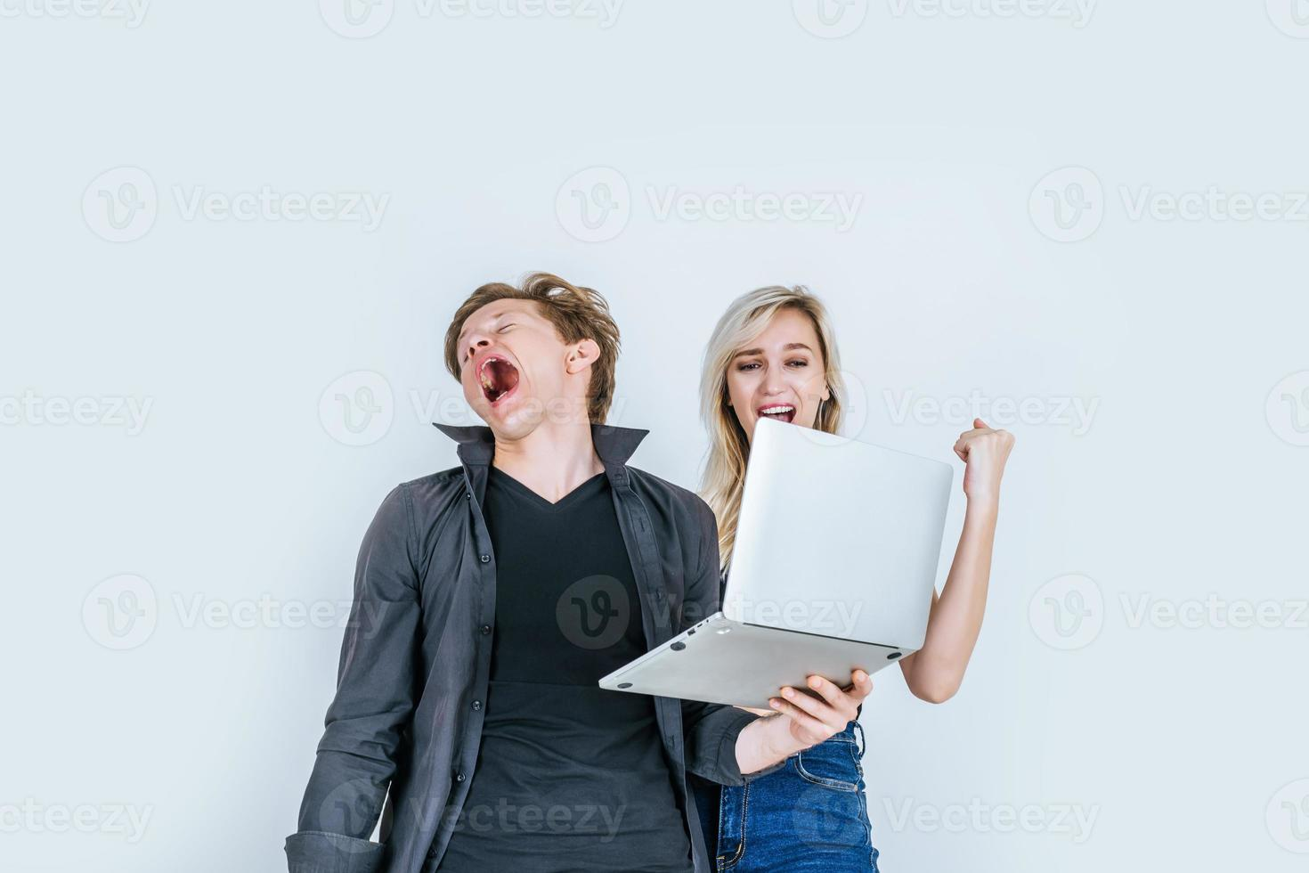 Porträt des glücklichen jungen Paares unter Verwendung des Laptops im Studio foto
