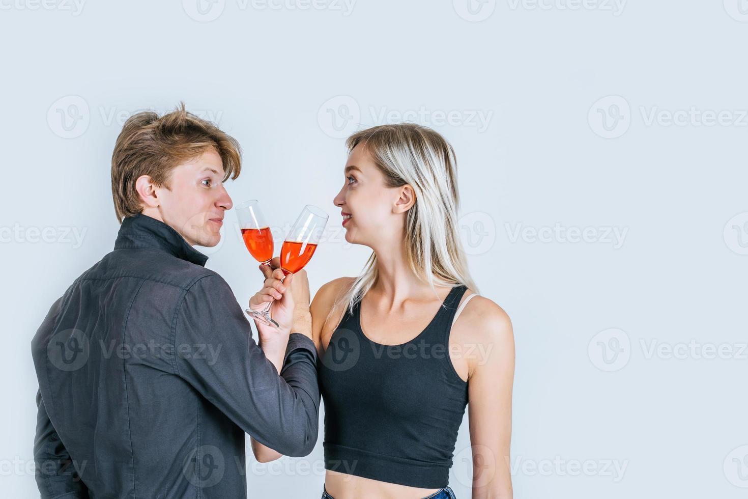 Porträt des glücklichen jungen Paares, das Wein im Studio trinkt foto