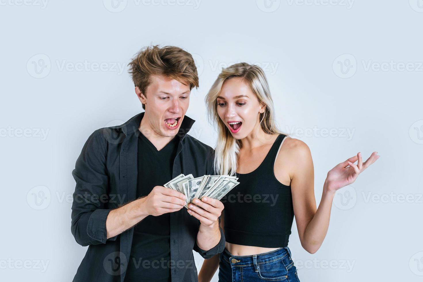 glückliches Paar, das Dollarbanknoten zeigt foto