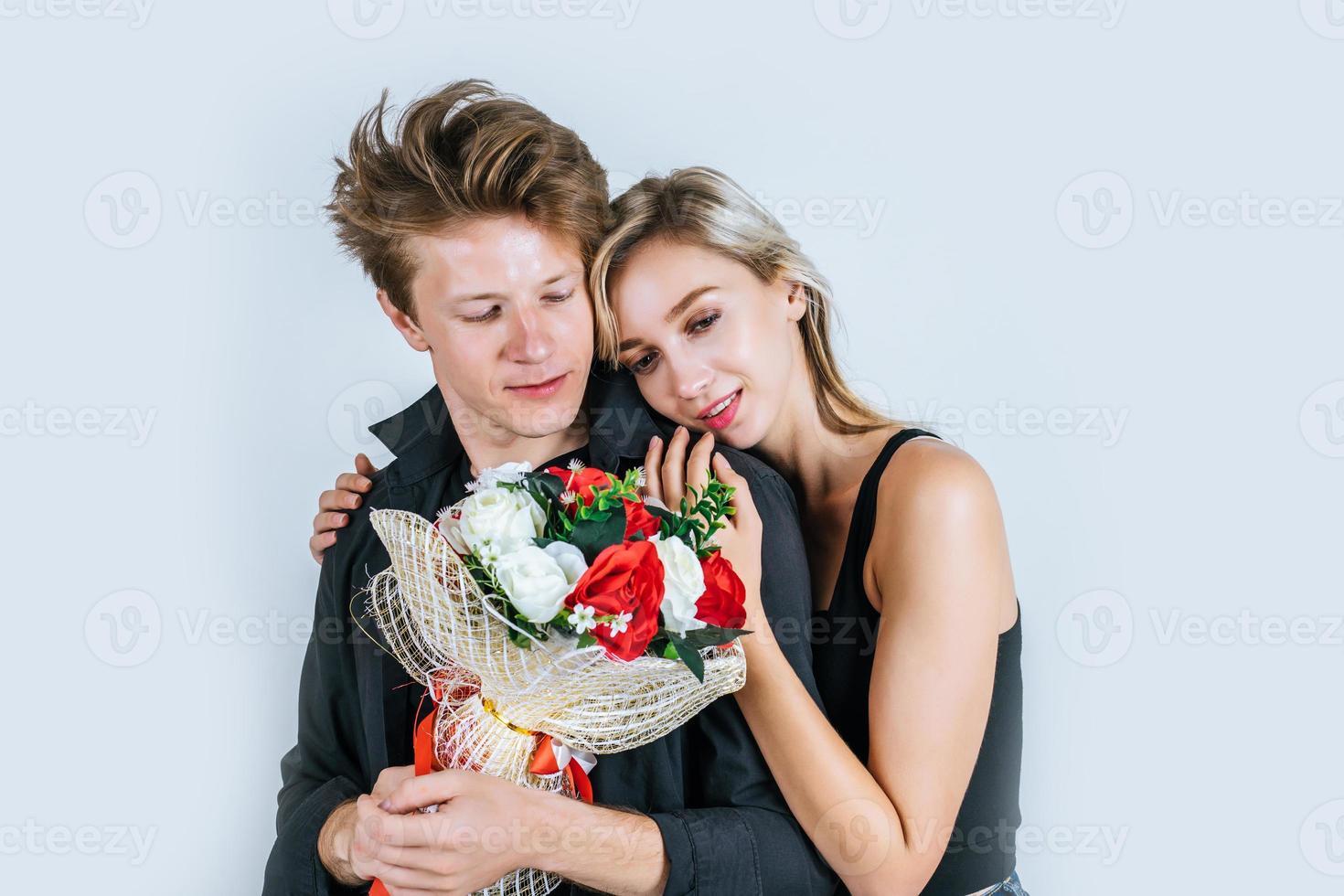 Porträt des glücklichen jungen Paares mit Blumen im Studio foto