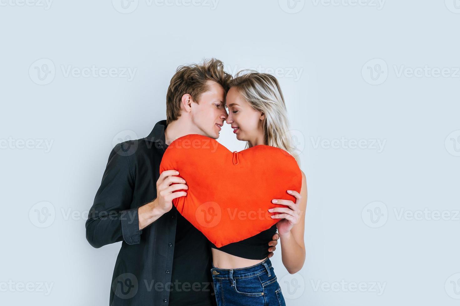glückliches Paar, das zusammen liebt, ein rotes Herz haltend foto