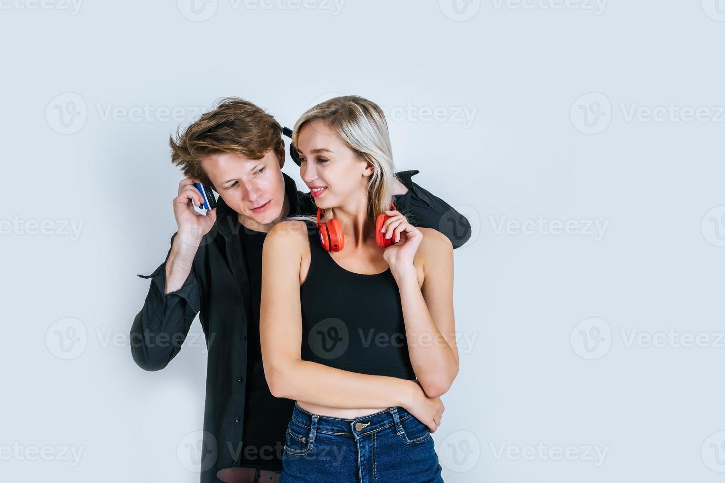 glückliches junges Paar in Kopfhörern, die Musik im Studio hören foto
