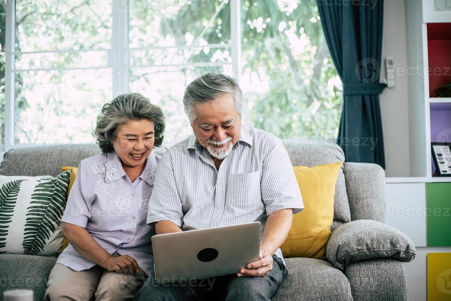 älteres Paar, das spricht und Laptop-Computer benutzt foto