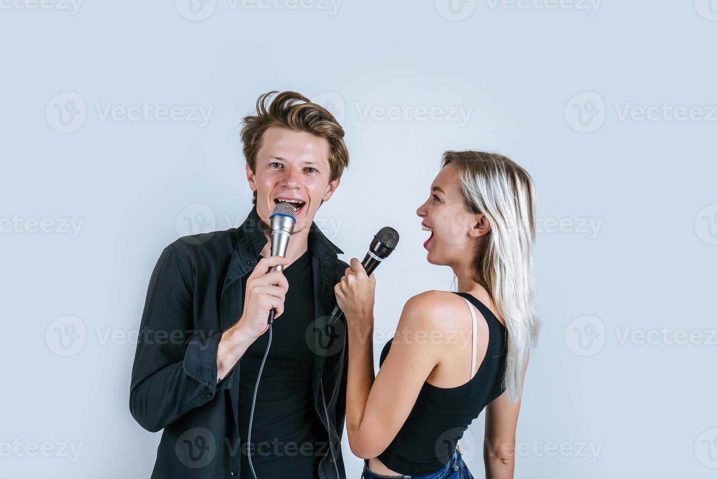 glückliches Porträt des Paares, das Mikrofone hält und singt foto