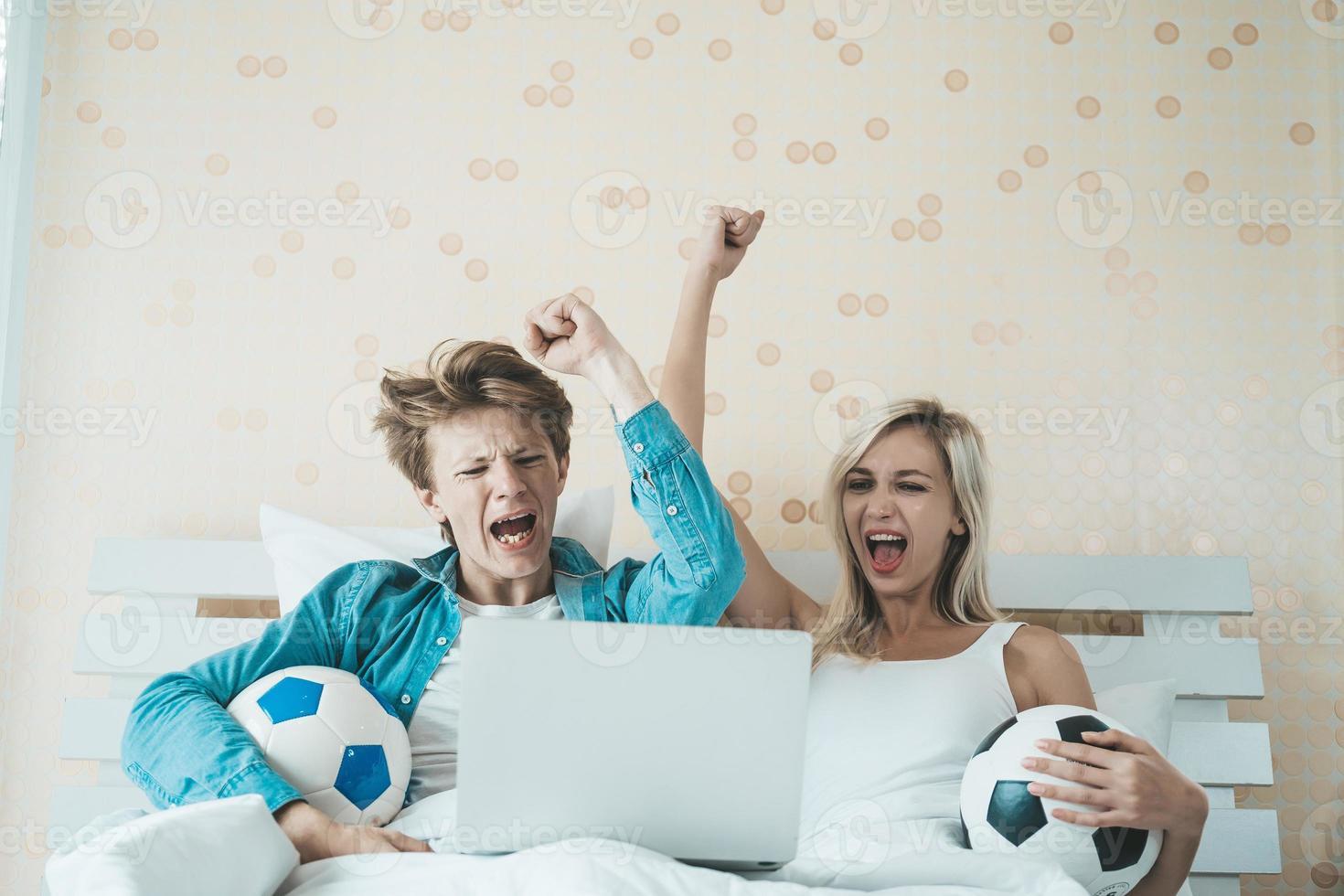 glückliches Paar, das Fußball auf dem Bett sieht foto