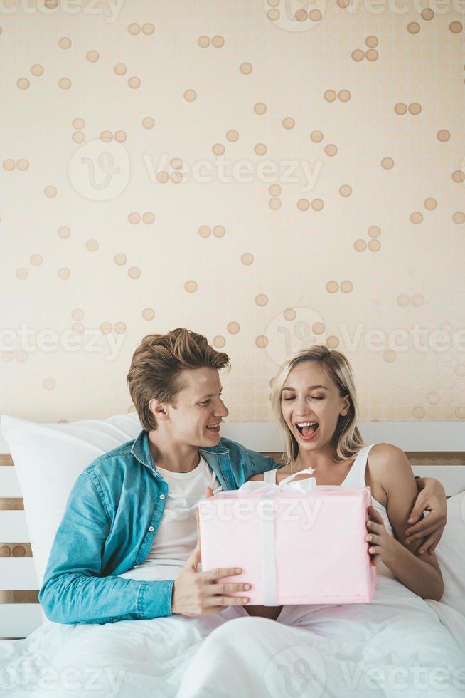 Freund überrascht seine Freundin mit einer Geschenkbox auf dem Bett foto