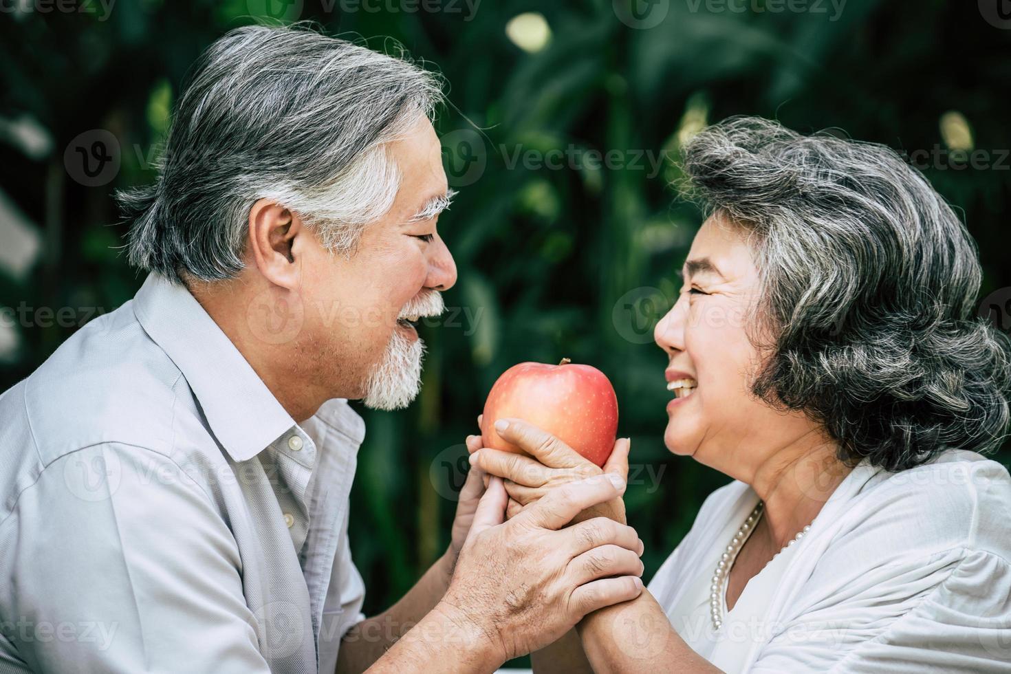 älteres Ehepaar, das etwas Obst spielt und isst foto