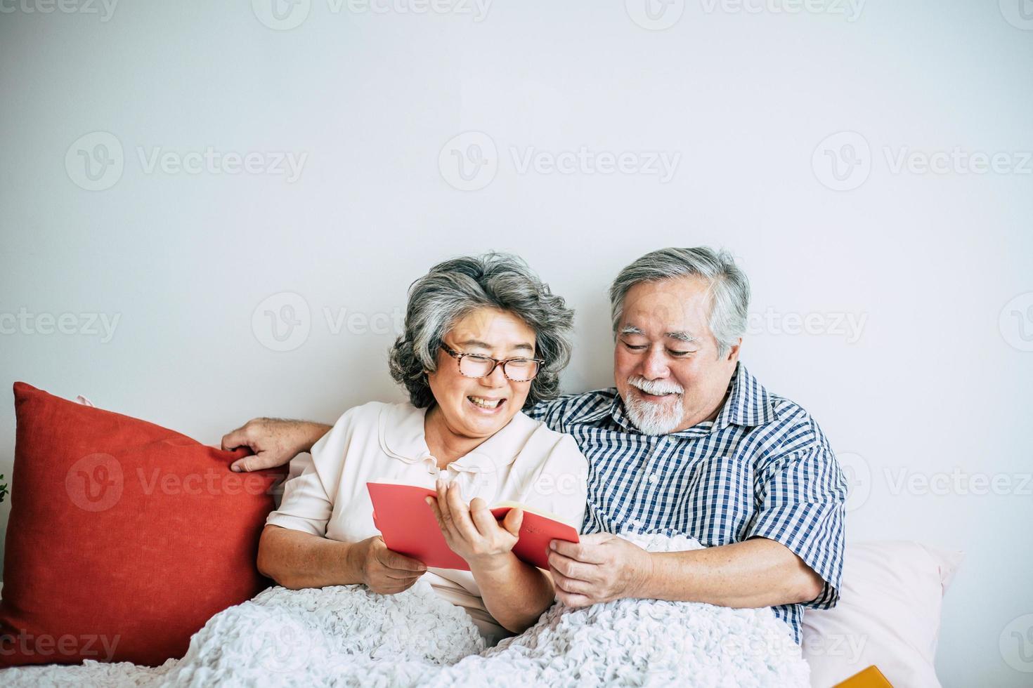 älteres Ehepaar, das auf dem Bett liegt und ein Buch liest foto