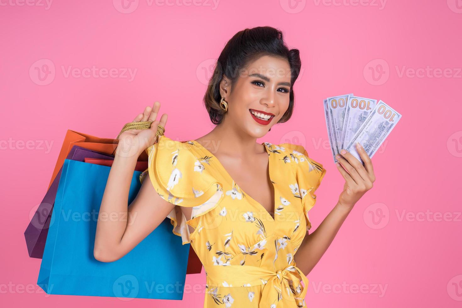 glückliche f modische Frau, die Geld für das Einkaufen hält foto