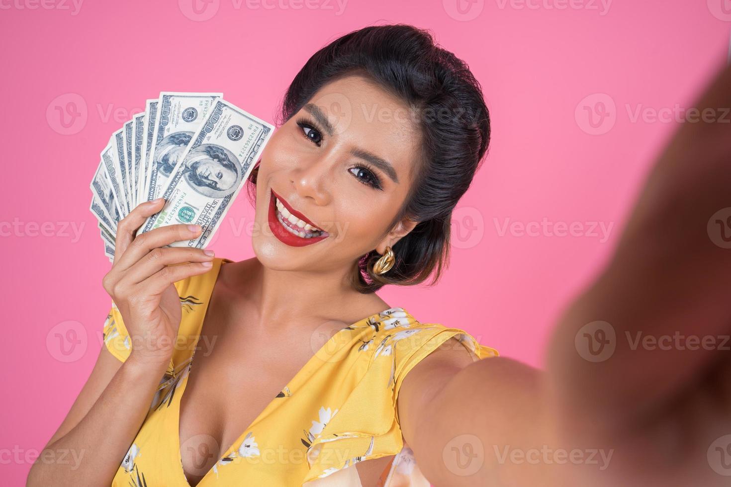 glückliche modische Frau, die Geld hält foto