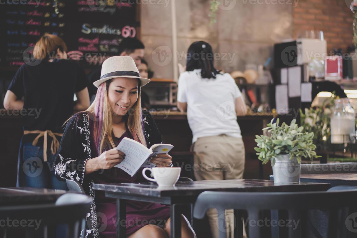 glückliche Geschäftsfrau, die ein Buch liest, während sie im Café entspannt foto
