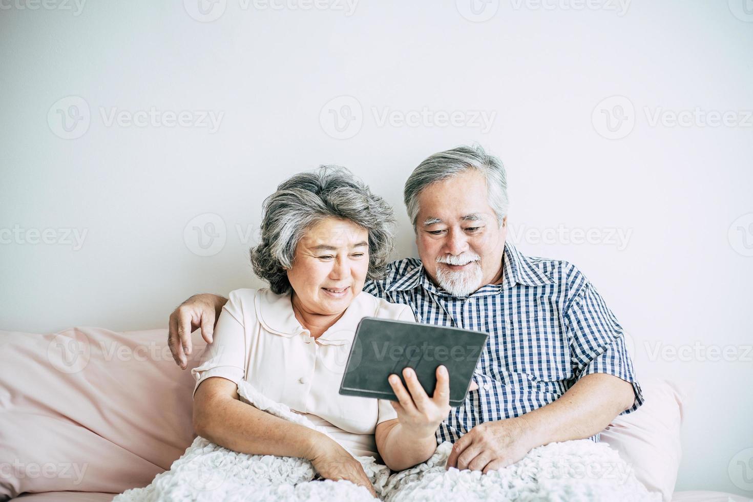 älteres Ehepaar mit einem Tablet-Computer foto