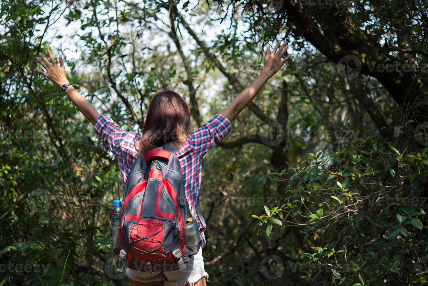 Wanderer mit Rucksack im Wald eines Berges mit erhobenen Händen foto