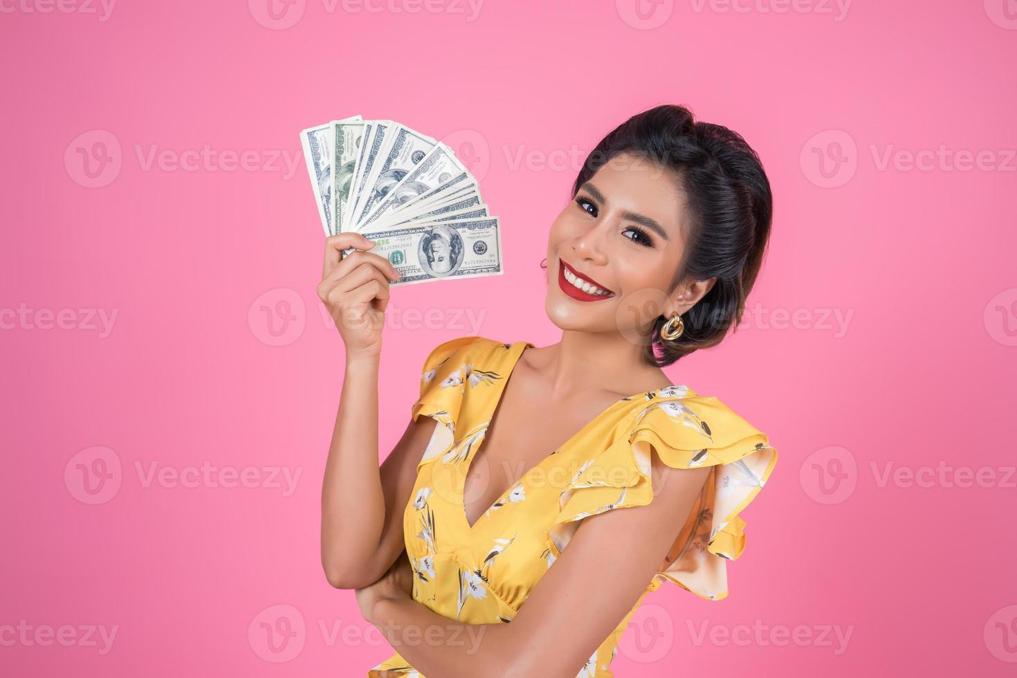 glückliche modische Frau, die Geld für das Einkaufen hält foto