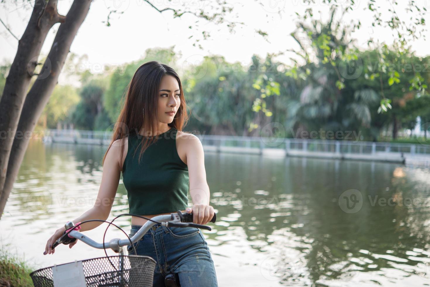 schöne junge Frau, die Fahrrad im grünen Park reitet foto