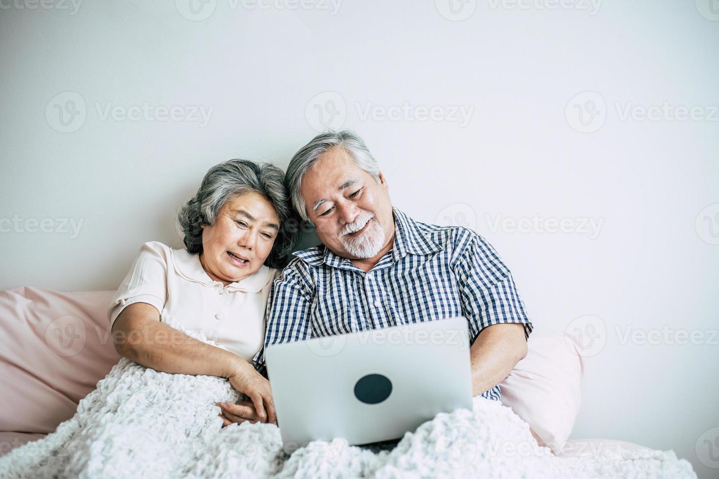 älteres Ehepaar spricht und benutzt Laptop im Schlafzimmer foto