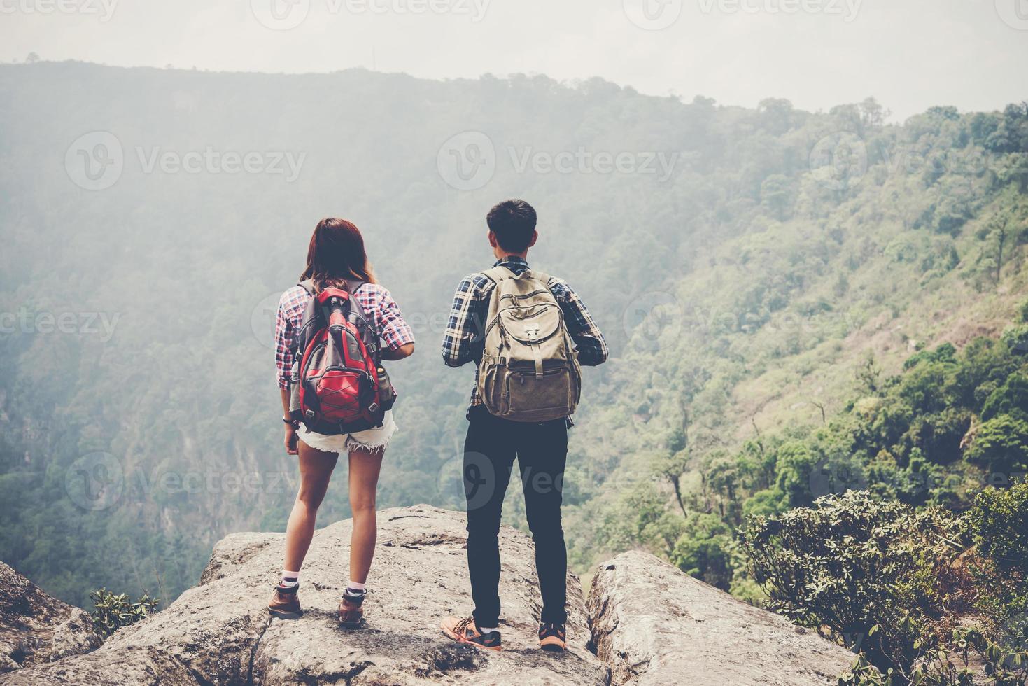 Wanderpaar mit Rucksäcken, die oben auf einem Berg stehen und Naturblick genießen foto