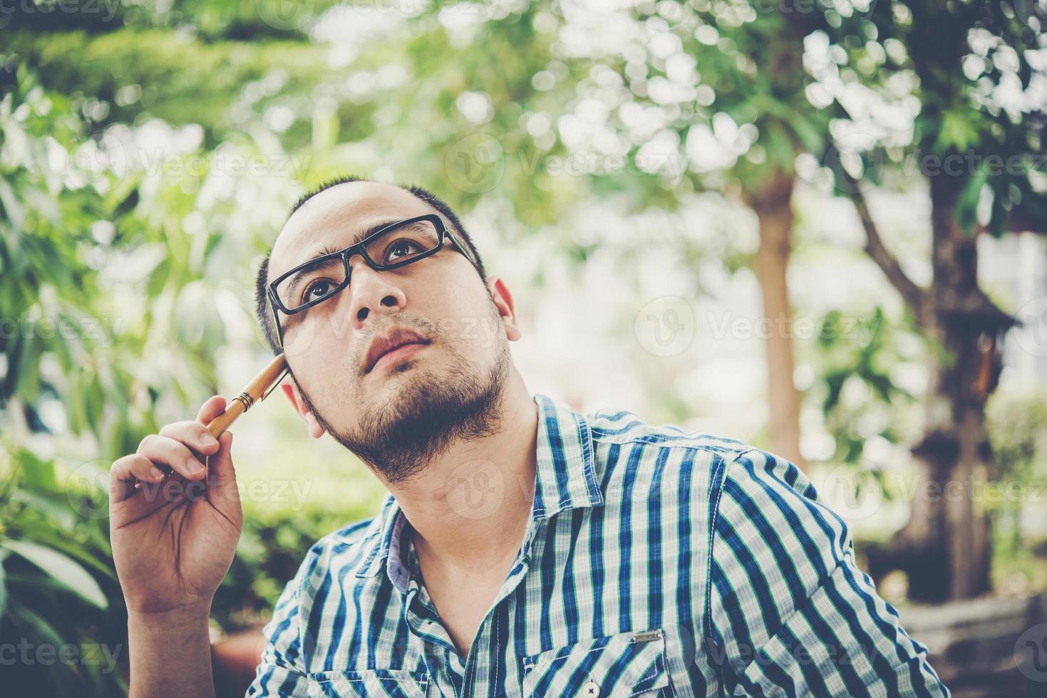 Geschäftsmann denkt über etwas mit Bleistift auf dem Kopf nach, während er zu Hause arbeitet foto
