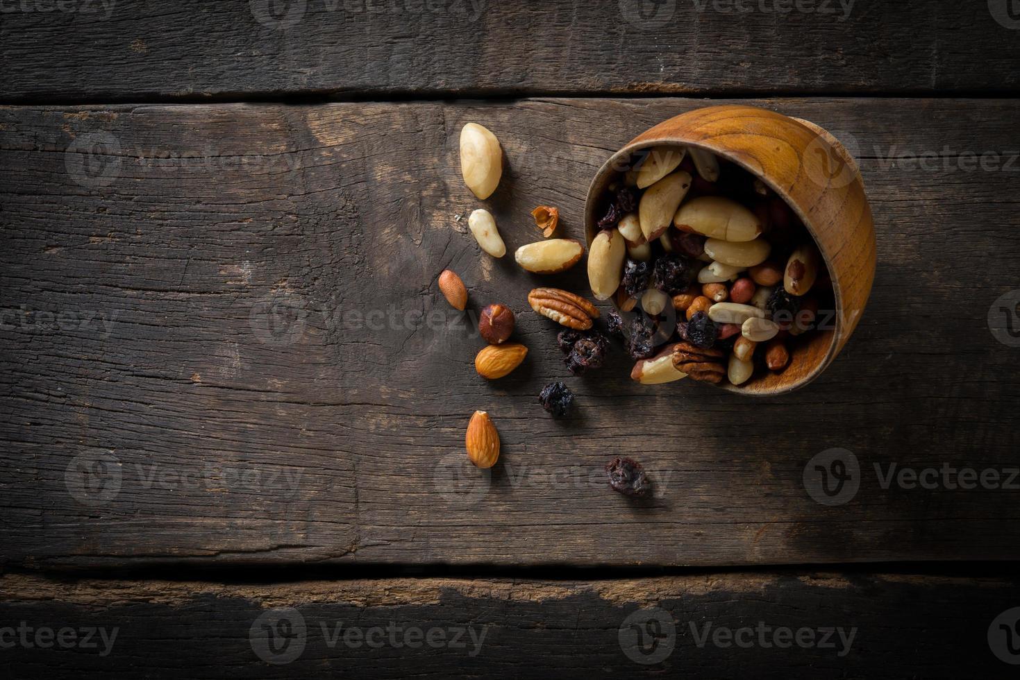 Nahaufnahme von gemischten Nüssen, die aus einer Schüssel auf hölzernem Hintergrund gießen foto