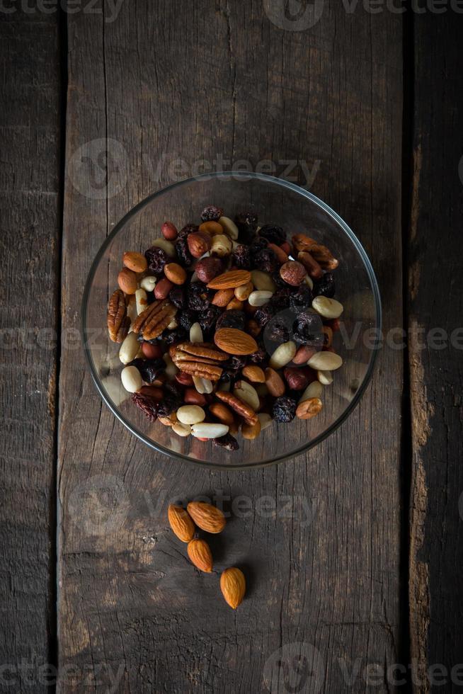gemischte Nüsse, die aus einer Schüssel auf hölzernem Hintergrund gießen foto