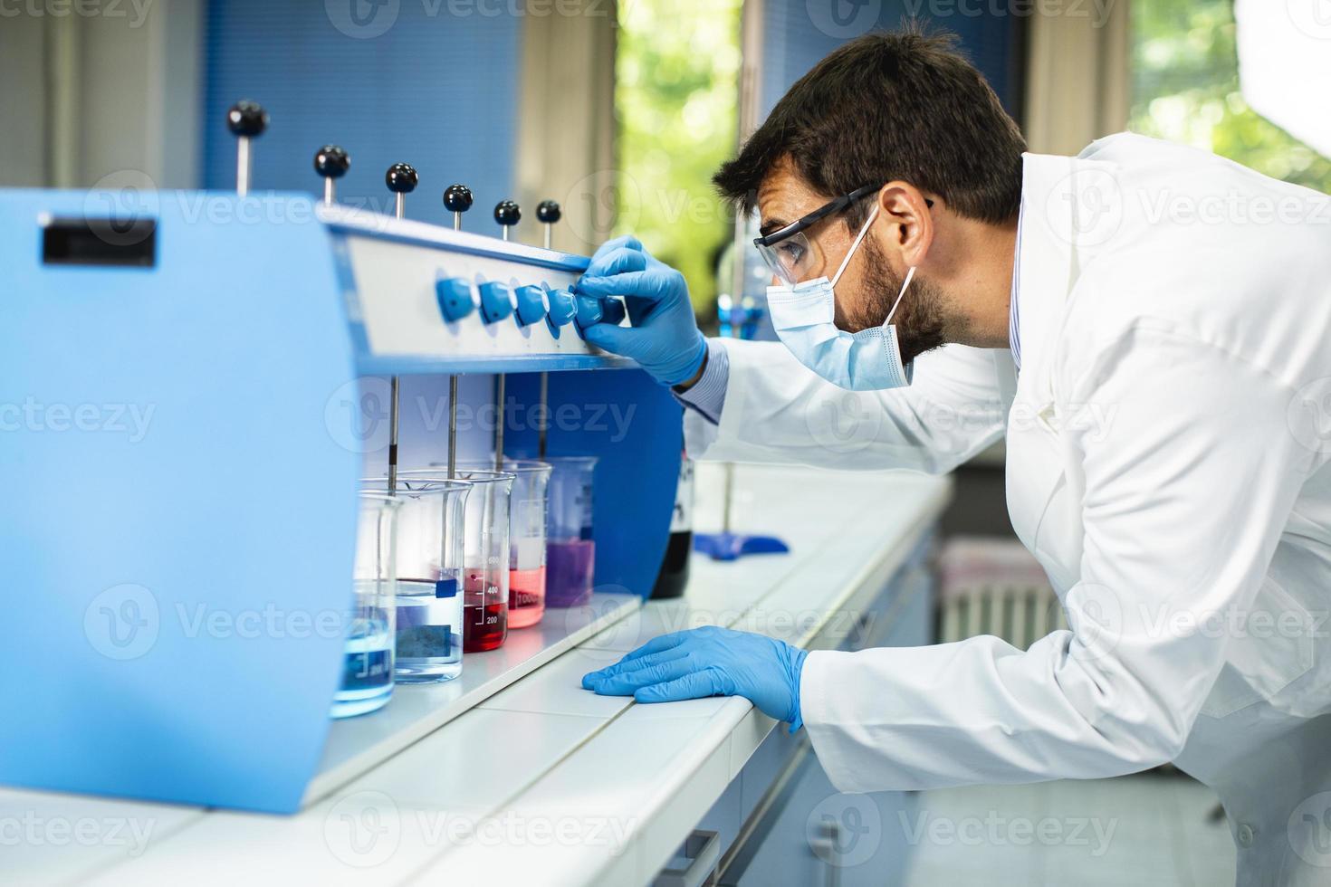 junger Forscher mit Schutzbrille, der Reagenzgläser im Flockungsmittel überprüft foto