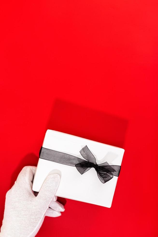 behandschuhte Hand, die ein Geschenk auf rotem Hintergrund hält. Kopierplatz für Text foto