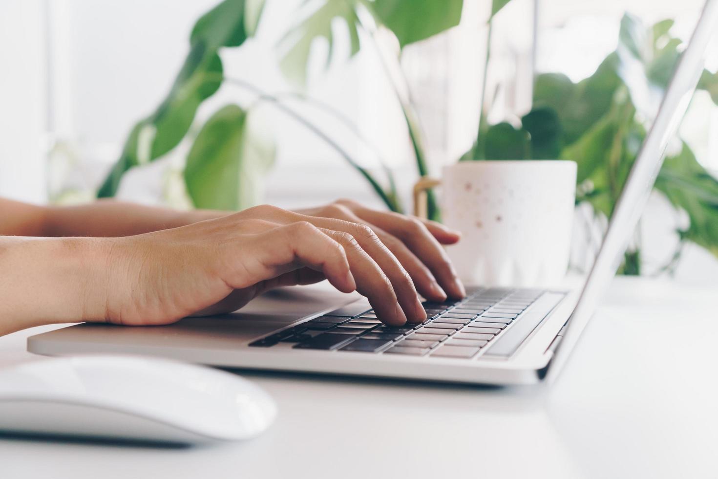 Person, die einen Laptop benutzt, um am Schreibtisch zu lernen foto
