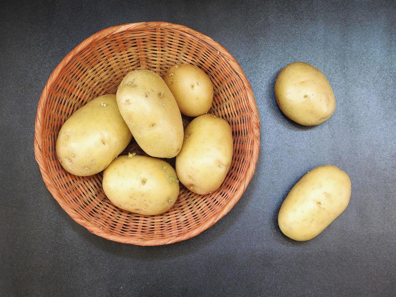 Kartoffeln in einem Weidenkorb auf einem dunklen Tischhintergrund foto