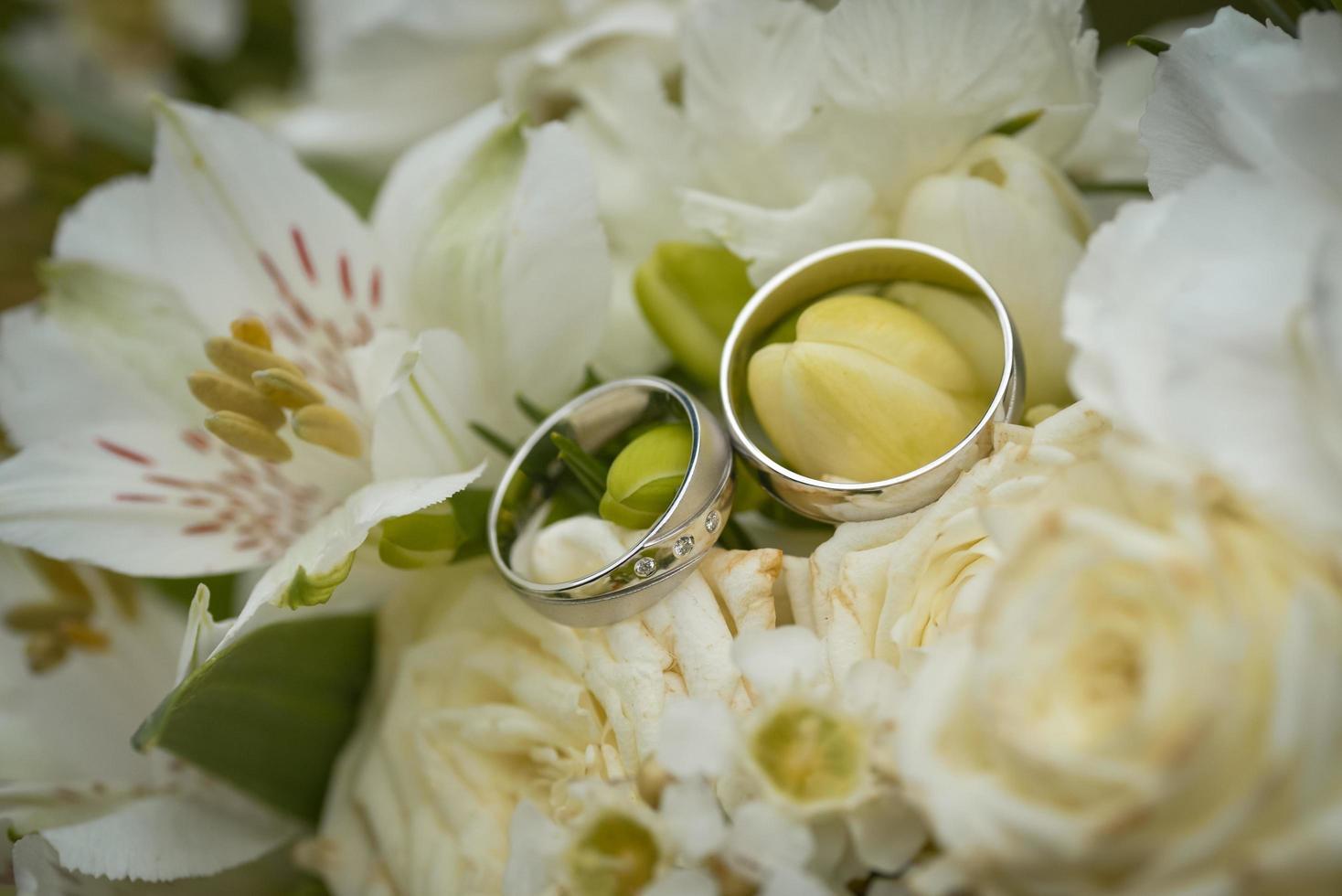 Eheringe auf einem Strauß weißer Blumen foto