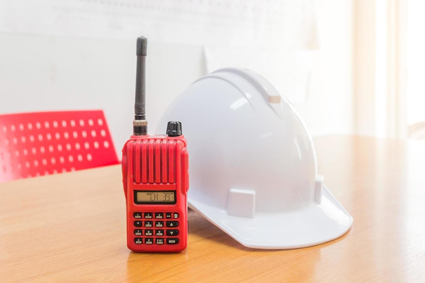 rotes Walkie-Talkie-Radio und weißer Schutzhelm foto