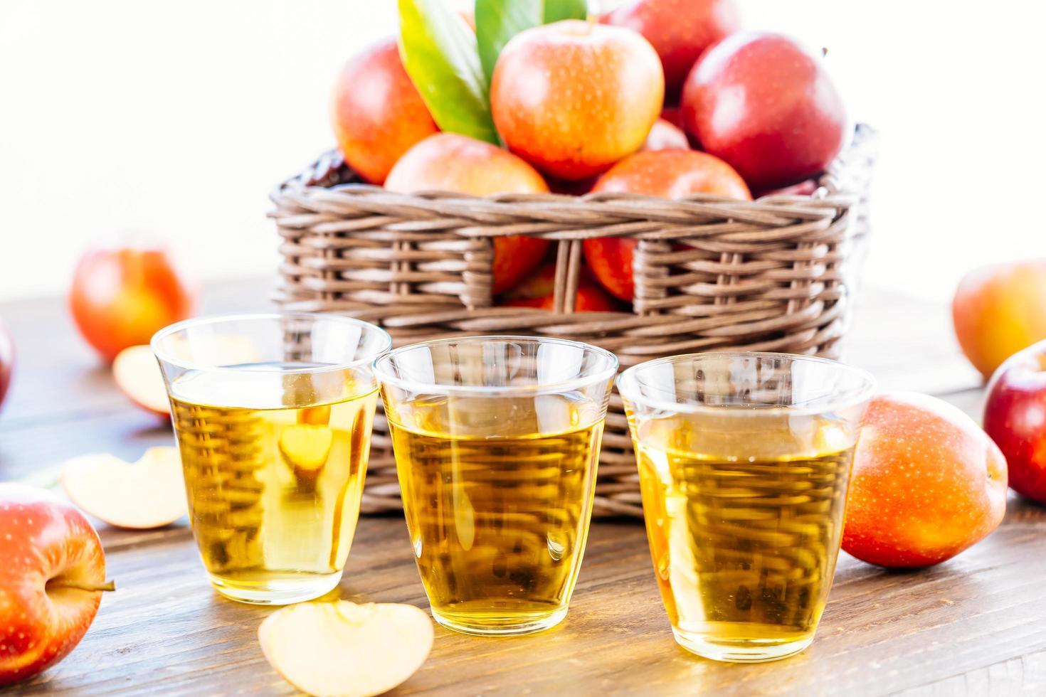 Apfelsaft in Gläsern und Äpfeln im Korb foto