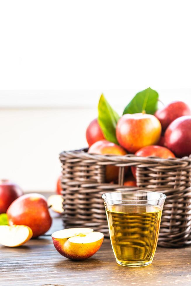 Apfelsaft in Glas und Äpfel im Korb foto