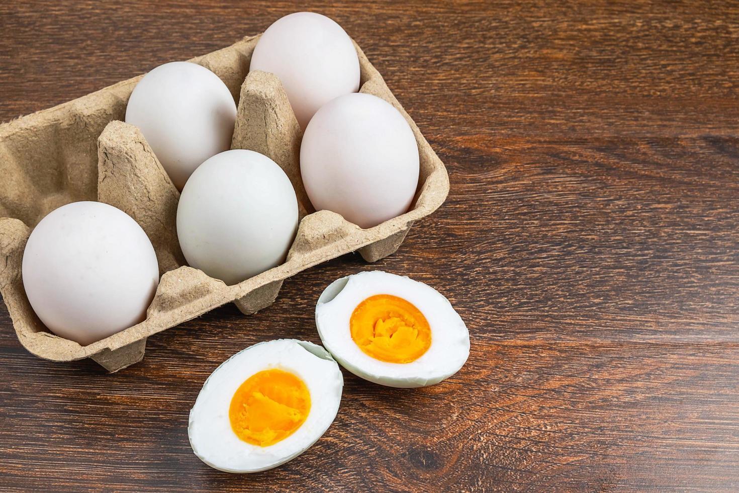 hart gekochtes Entenei in Scheiben geschnitten neben ganzen Eiern in einem Karton auf einem Holztisch foto