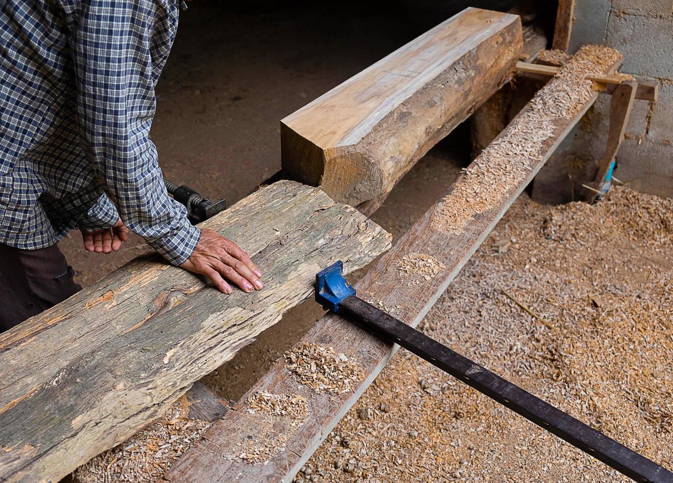 Mann, der eine Holzplanke in einer Holzbearbeitungswerkstatt justiert foto