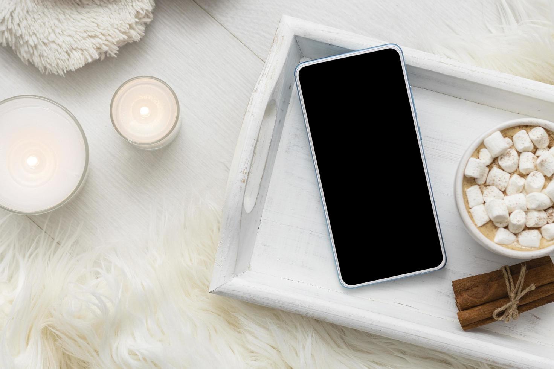 Smartphone-Modell mit heißer Schokolade foto