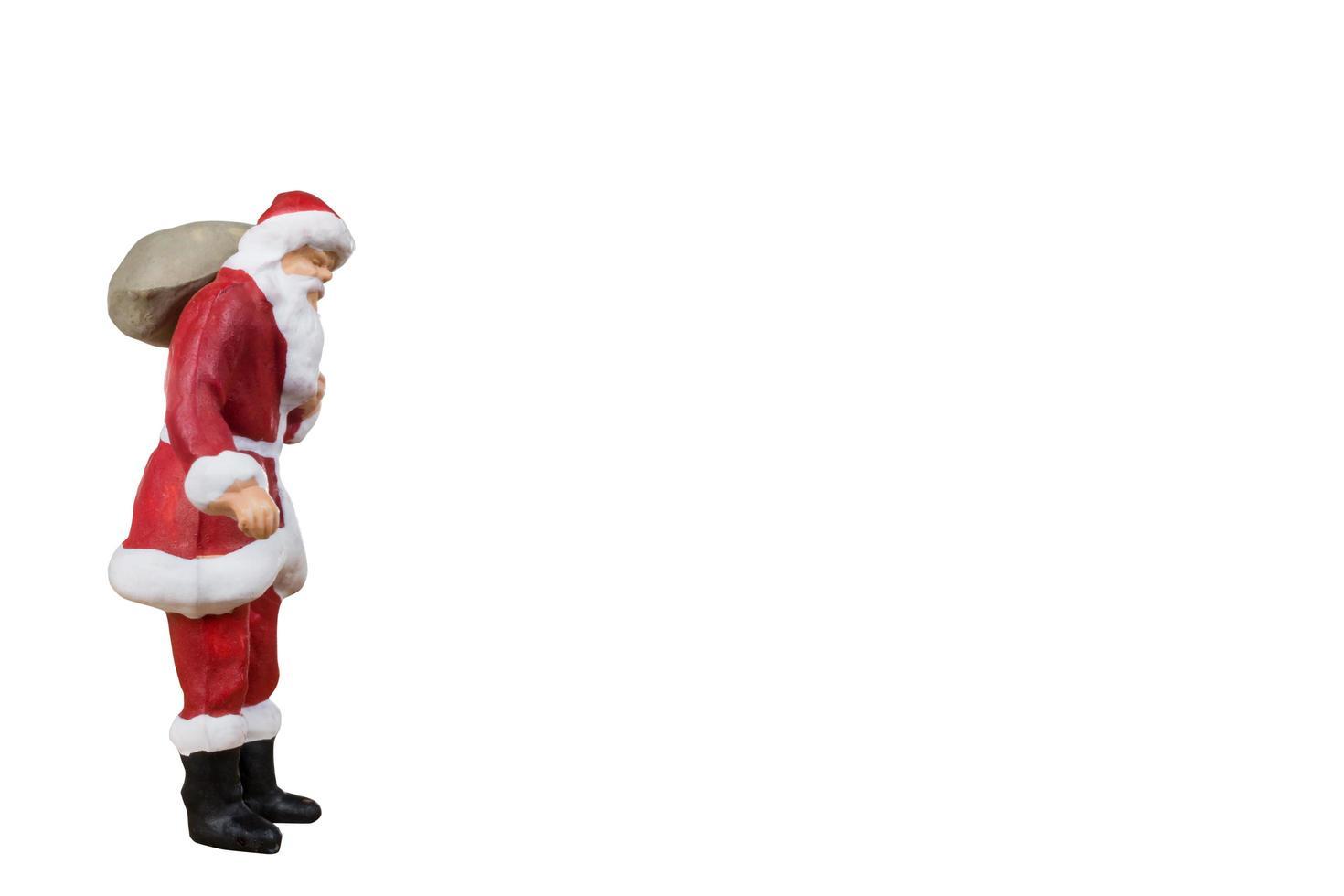 Miniatur-Weihnachtsmann, der eine Tasche trägt, die auf einem weißen Hintergrund lokalisiert wird foto