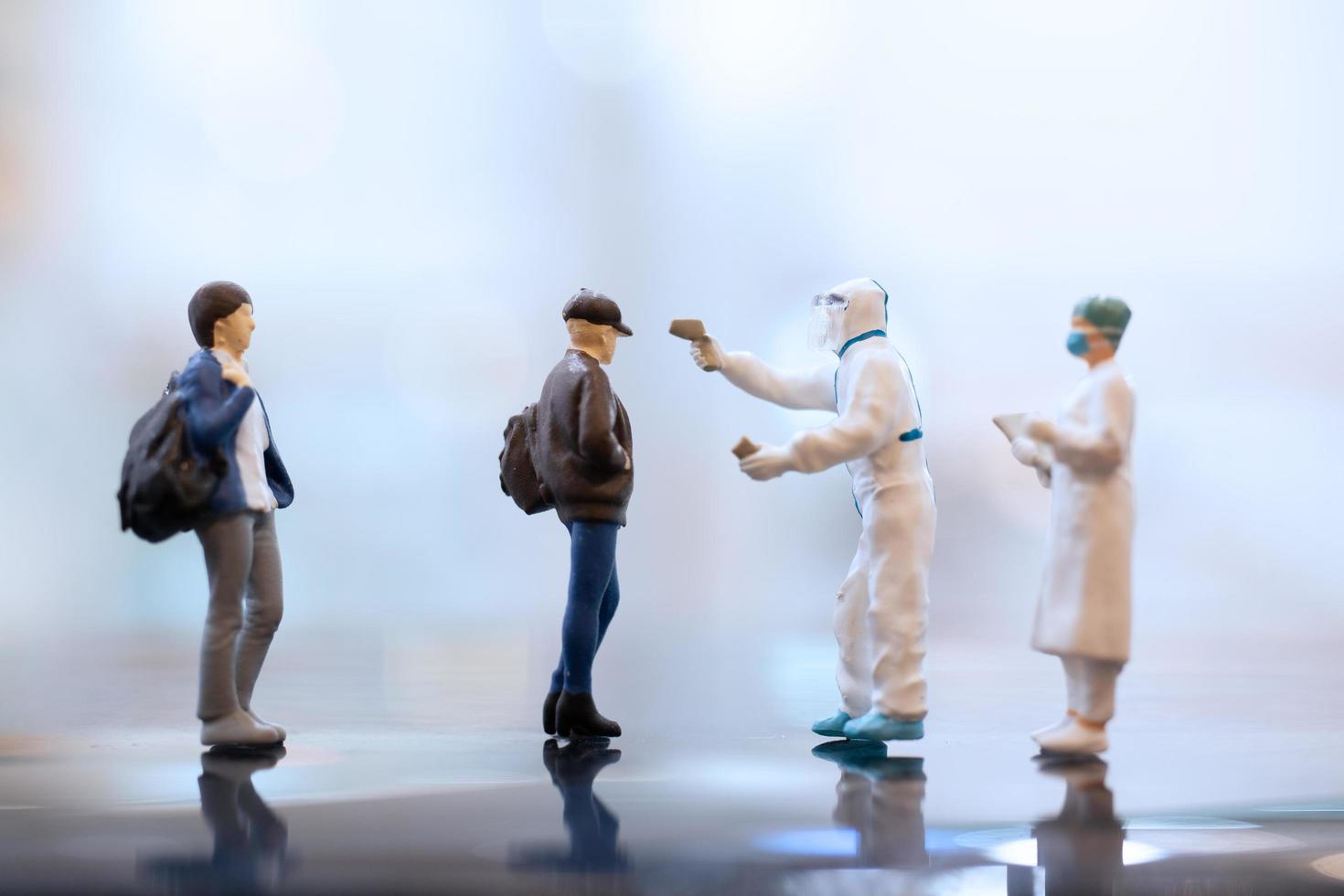 Miniaturarzt, der eine Gesichtsmaske während des Coronavirus- und Grippeausbruch-, Virus- und Krankheitsschutzkonzepts trägt foto