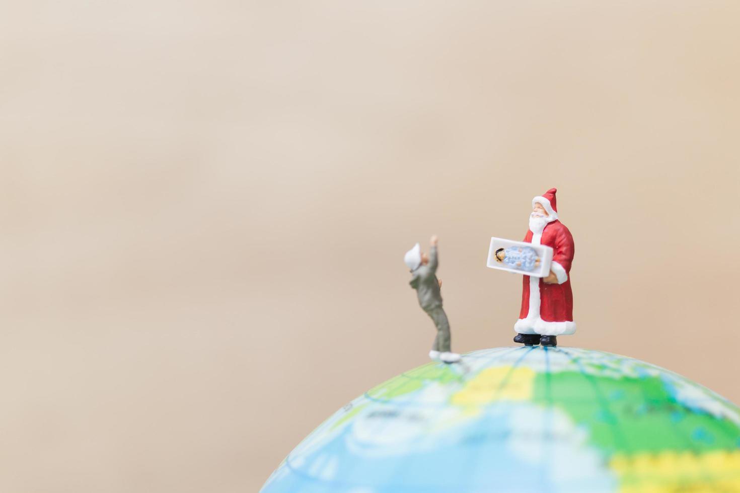 Miniatur-Weihnachtsmann, der Geschenke für Kinder auf einem Globus hält, frohe Weihnachtskonzept foto