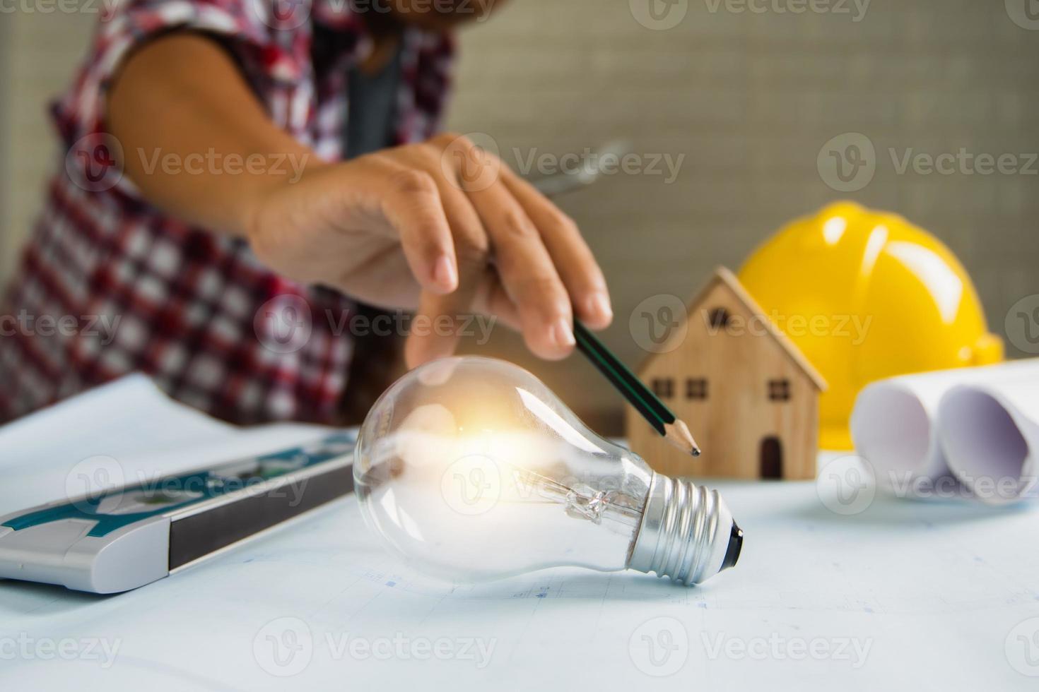Mann mit Bleistiftspitze zum Anzünden der Glühbirne neben dem Hausmodell, dem Schutzhelm und den aufgerollten Papieren foto