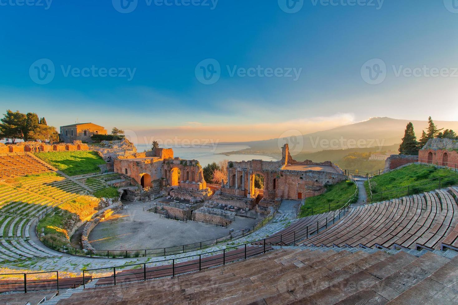 altes Theater von Taormina mit Ätna ausbrechendem Vulkan bei Sonnenuntergang foto
