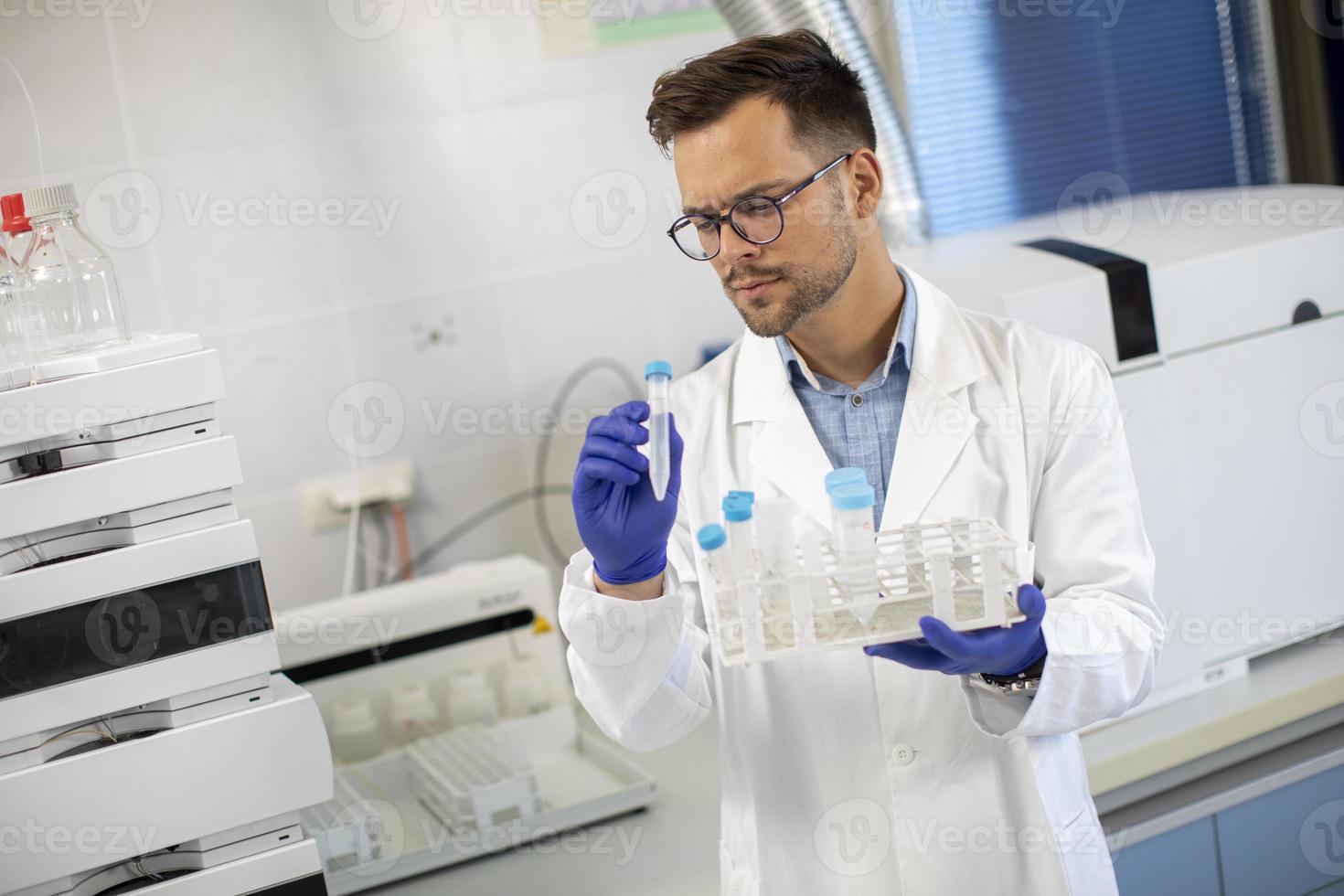 junger Forscher, der im Labor mit chemischen Proben arbeitet foto